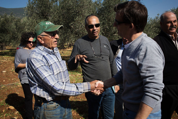 Olive farmer Abu Naim (left) shakes hands with Dave Harden, USAID mission director in the Palestinian Authority