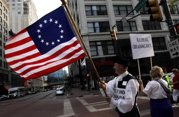 Paul Wheeler waves a flag while standing with a small group of demonstrators outside of the HIlton Hotel and Suites prior to former South Carolina Senator Jim DeMint, president of the The Heritage Foundation, speaking at a ''Defund Obamacare Tour'' rally in Indianapolis August 26, 2013. Credit: Reuters/Nate Chute