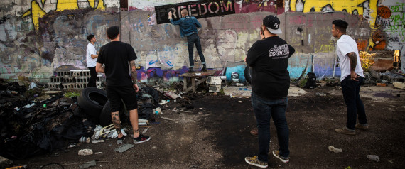 """DETROIT, MI - SEPTEMBER 04:  Members of the band """"Freedom"""" spray paint their name on a wall at the abandoned Packard Automotive Plant on September 4, 2013 in Detroit, Michigan. (Photo by Andrew Burton/Getty Images)"""