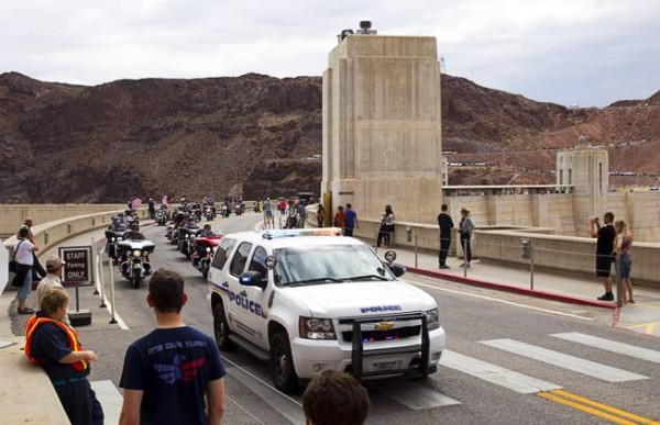 A Dam Police vehicle leads hundreds of motorcyclists over Hoover Dam during the annual Flags Over the Dam parade Sunday, May 24, 2015, from the dam to Southern Nevada Veterans Memorial Cemetery.