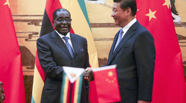 Zimbabwe's President Robert Mugabe (L) and his Chinese counterpart Xi Jinping shake hands during a signing ceremony at the Great Hall of the People in Beijing August 25, 2014. REUTERS/Diego Azubel/Pool (CHINA - Tags: POLITICS) - RTR43NIT