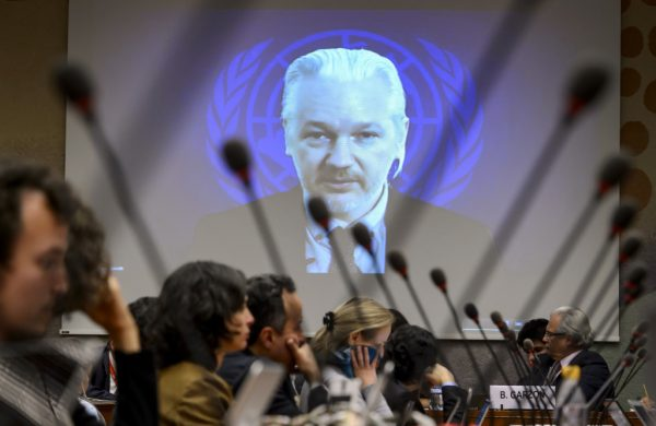 WikiLeaks founder Julian Assange is seen on a screen speaking via web cast from the Ecuadorian Embassy in London during an event on the sideline of the United Nations (UN) Human Rights Council session on March 23, 2015 in Geneva. Assange took refuge in June 2012 in the Ecuadorian Embassy to avoid extradition to Sweden, where he faces allegations of rape and sexual molestation, which he strongly denies. AFP PHOTO / FABRICE COFFRINI (Photo credit should read FABRICE COFFRINI/AFP/Getty Images)