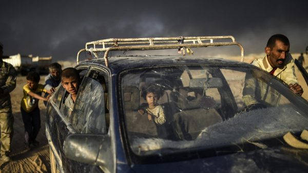 AFP PICTURES OF THE YEAR 2016 Displaced Iraqis arrive at refugee camp on October 22, 2016 in the town of Qayyarah, south of Mosul, as an operation to recapture the city of Mosul from the Islamic State group takes place. Iraqi security forces battled for a second day with Islamic State group gunmen who infiltrated Kirkuk in a brazen raid that rattled Iraq as it ramped up an offensive to retake Mosul. / AFP PHOTO / BULENT KILIC