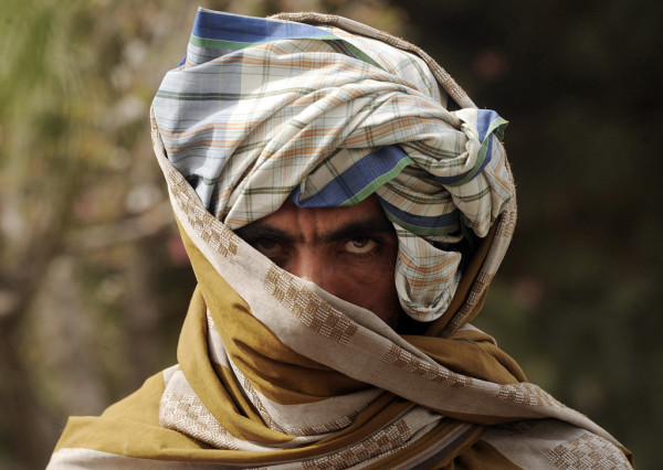 A former Taliban fighter looks on after