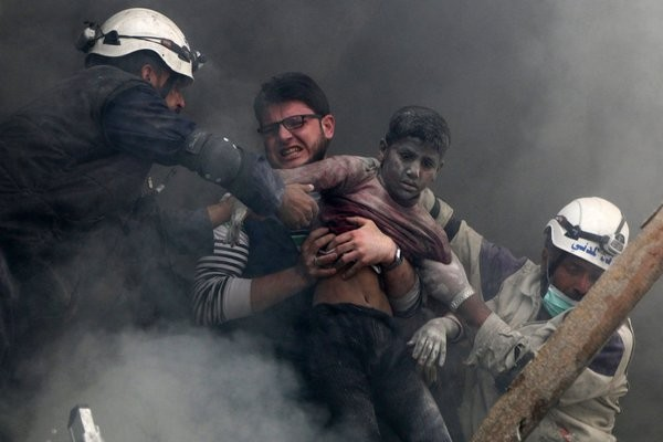A boy was pulled from the rubble after a barrel bomb attack in Aleppo, Syria, last year. Credit Hosam Katan/Reuters