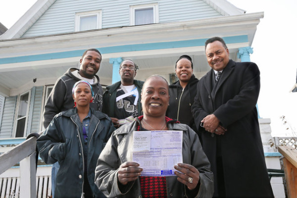 Aretha Robertson holds her property tax bill Wednesday with a receipt marked paid. To save her home from foreclosure, her neighbors raised money and the city treasurer's office reached out to a banker for a loan. With Robertson are neighbor Billie Hintz (from left), son Marco Pollard, husband Michael Robertson, neighbor Sandra Cooper, and Milwaukee Treasurer Spencer Coggs.