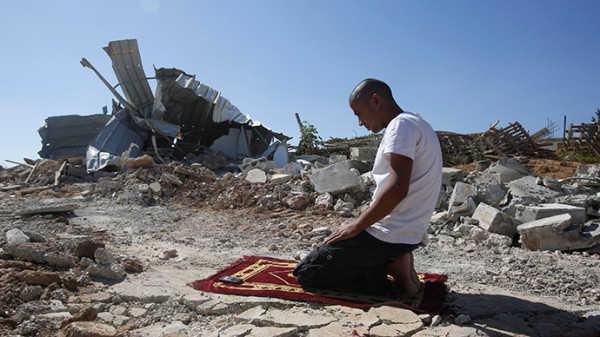 A Palestinian Bedouin near his dwelling that was demolished by Israeli bulldozers near the Jewish settlement of Karmel, near the West Bank city of Hebron (Reuters / Mussa Qawasma)
