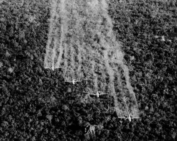 "A photo provided by the U.S. Air Force shows four ""Ranch Hand"" C-123 aircraft spraying liquid defoliant on a suspected Viet Cong position in South Vietnam, September 1965. The four specially equipped planes covered a 1,000-foot-wide swath in each pass over the dense vegetation. (AP Photo.US Air Force)"