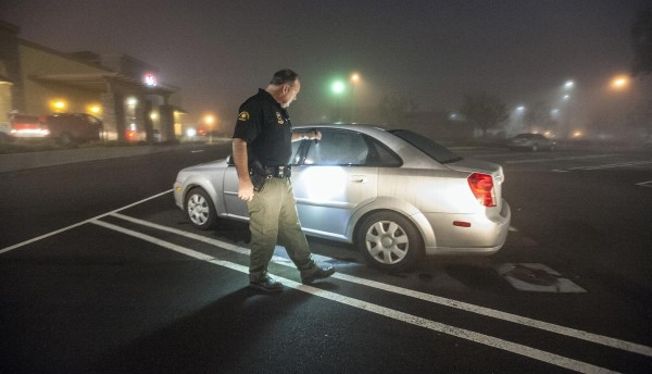 Orange County Deputy Sheriff Chet Parker, a homeless liaison officer, checks out a lone car in a parking lot just off of El Toro Road in Lake Forest just before dawn.   ///ADDITIONAL INFORMATION:  OC.homelessenforceÐ 02/03/15 Ð MARK RIGHTMIRE, ORANGE COUNTY REGISTER