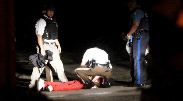 An unidentified man lies wounded while being detained by Ferguson police, Aug 9th. Rick Wilking / Reuters