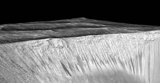 Dark narrow streaks called recurring slope lineae emanating out of the walls of Garni crater on Mars. Credits: NASA/JPL/University of Arizona