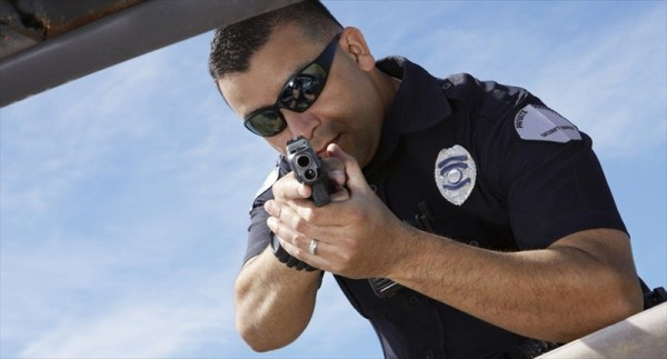 Police-Officer-Aiming-Gun-At-Broken-Car-Shutterstock-800x430