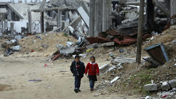 A Palestinian brother and sister walk in front of a building which was destroyed in last summer's Israel-Hamas war, in the Shijaiyah neighborhood of Gaza City, northern Gaza Strip, Monday, Feb. 23, 2015. (AP Photo/Adel Hana)
