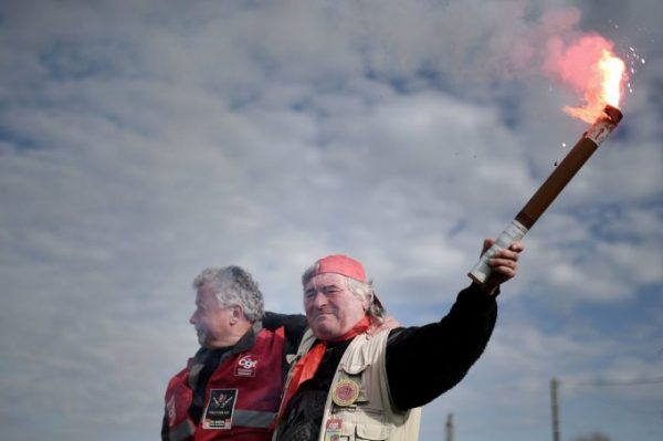 An employee of the France's national state-owned railway company (SNCF) raises a flare as they block the access to an oil depot near the Total refinery of Donges, western France, on May 25, 2016 to protest against the government's planned labour law reforms. France has been using strategic fuel reserves for two days in the face of widespread blockades of oil depots by union activists, the head of the oil industry federation said on May 25, 2016. / AFP / JEAN-SEBASTIEN EVRARD (Photo credit should read JEAN-SEBASTIEN EVRARD/AFP/Getty Images)
