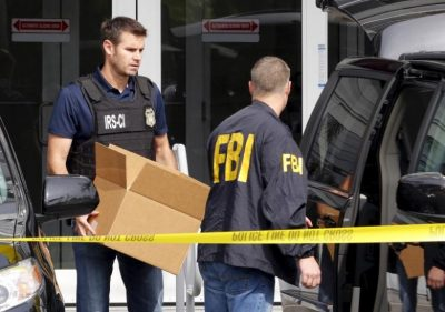 FBI agents remove boxes and other items from the offices of Imagina in Miami